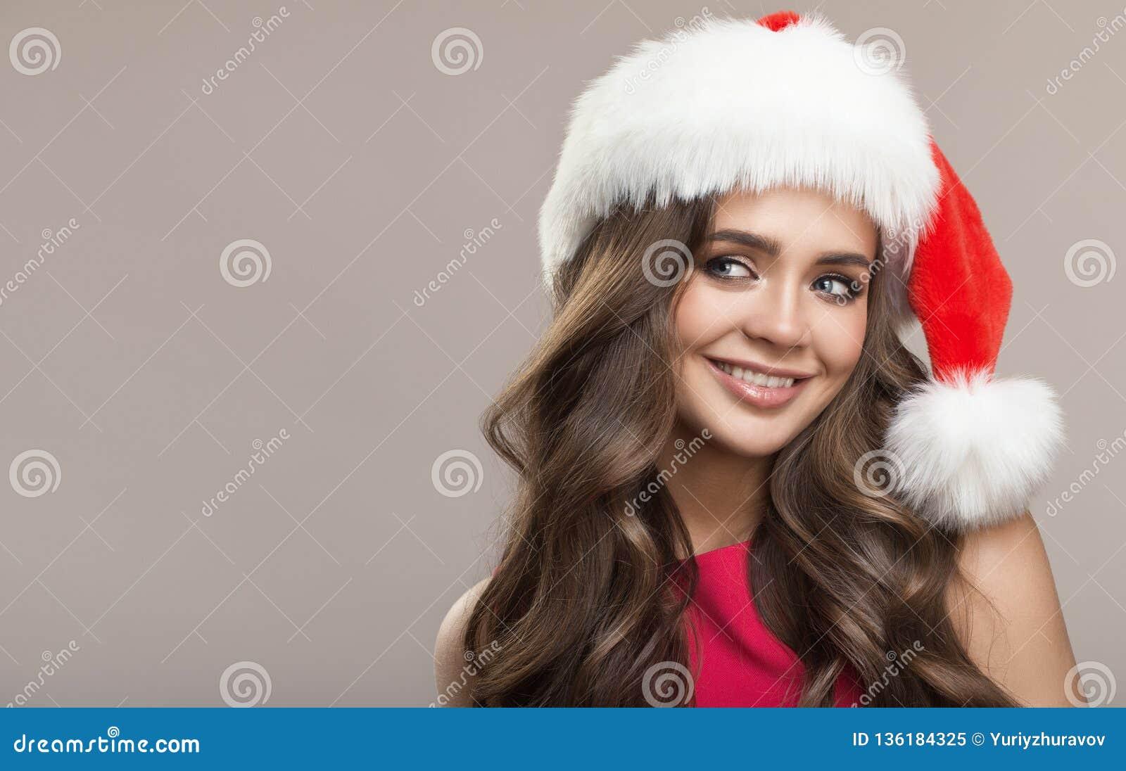Portret van aantrekkelijke leuke glimlachende vrouw in santahoed