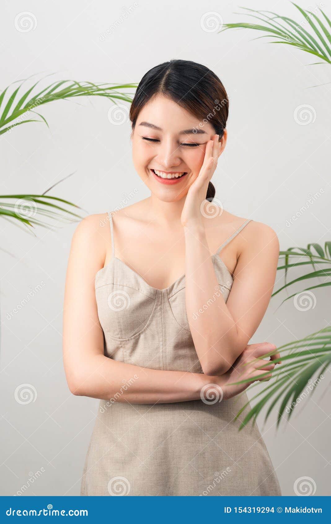 Portret van Aziatische gelukkige vrouw status met groene bladeren rond haar op witte achtergrond