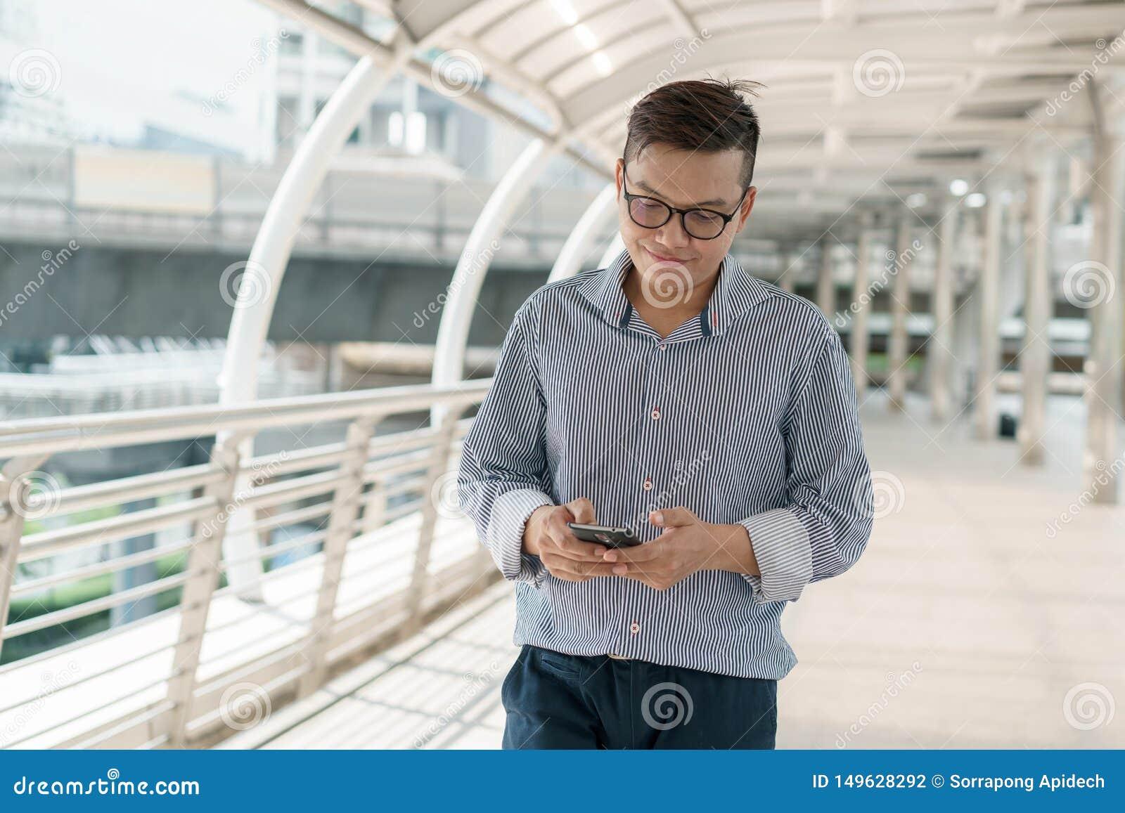 Portret van Aziatische jonge zakenman status op Buitenkantoor Het jonge kostuum die van de zakenmanslijtage en smartphone glimlac
