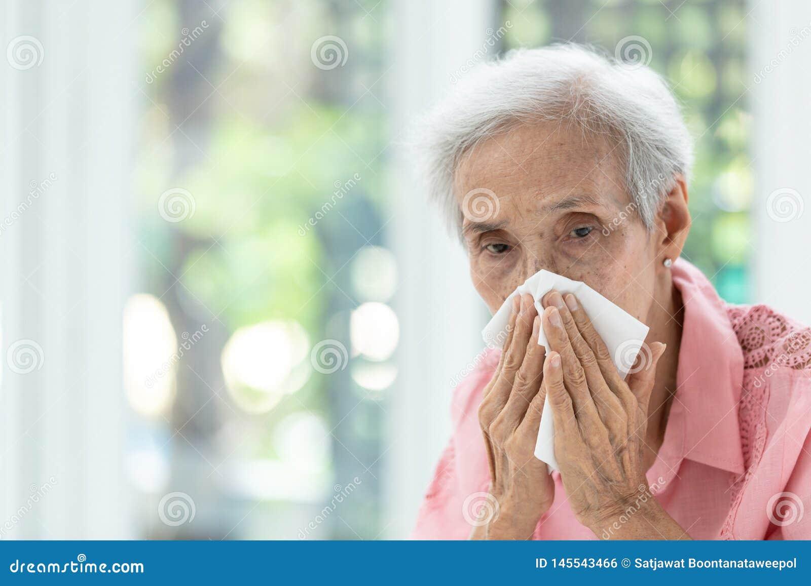 Portret van bejaarde blazende neus in document zakdoek, lopende neus die, Aziatische hogere vrouw in een weefsel, concept niezen