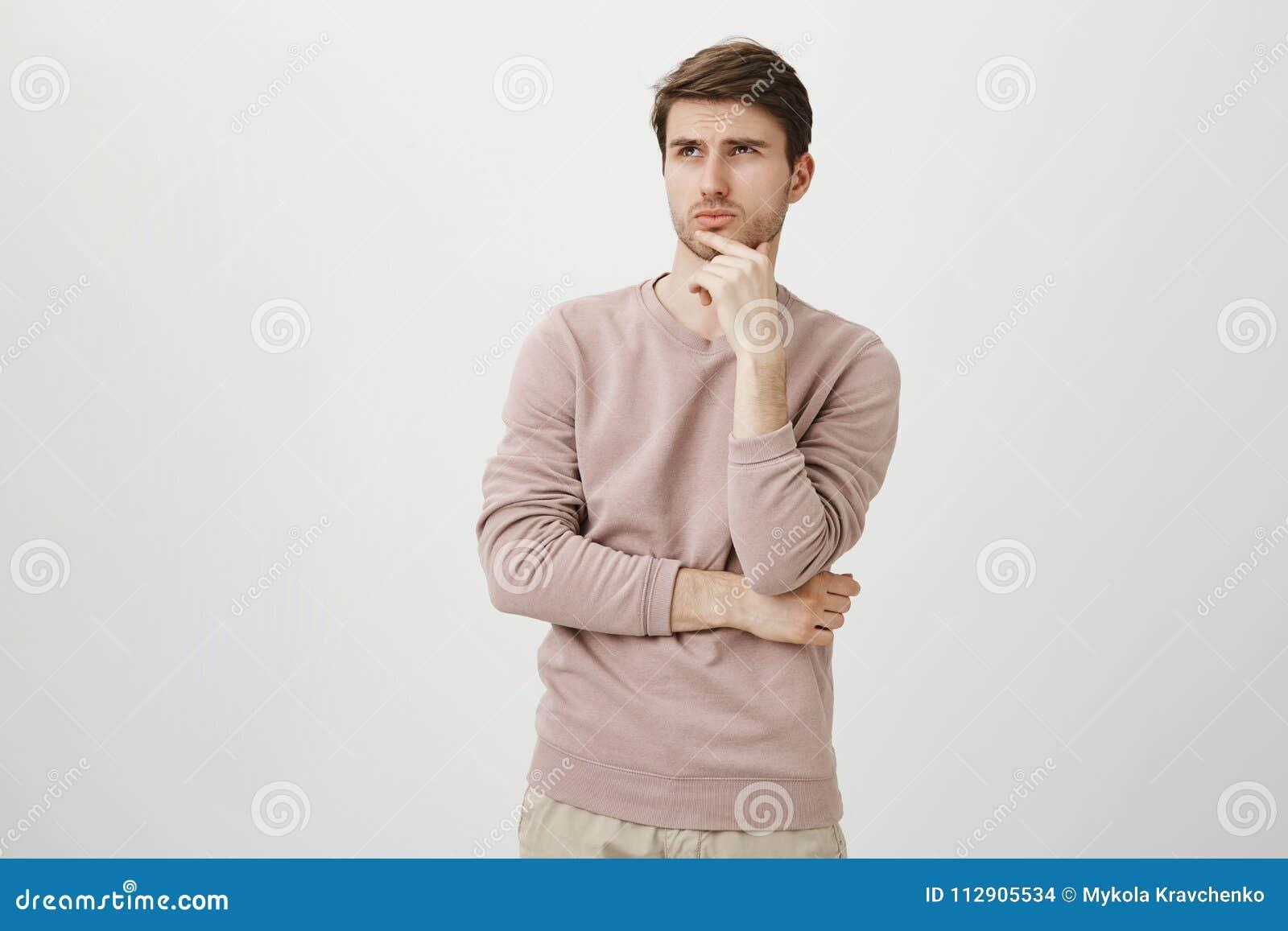 Portret van de aantrekkelijke jonge mens met varkenshaar die omhoog terwijl wat betreft kin en over iets denken eruit zien, die z