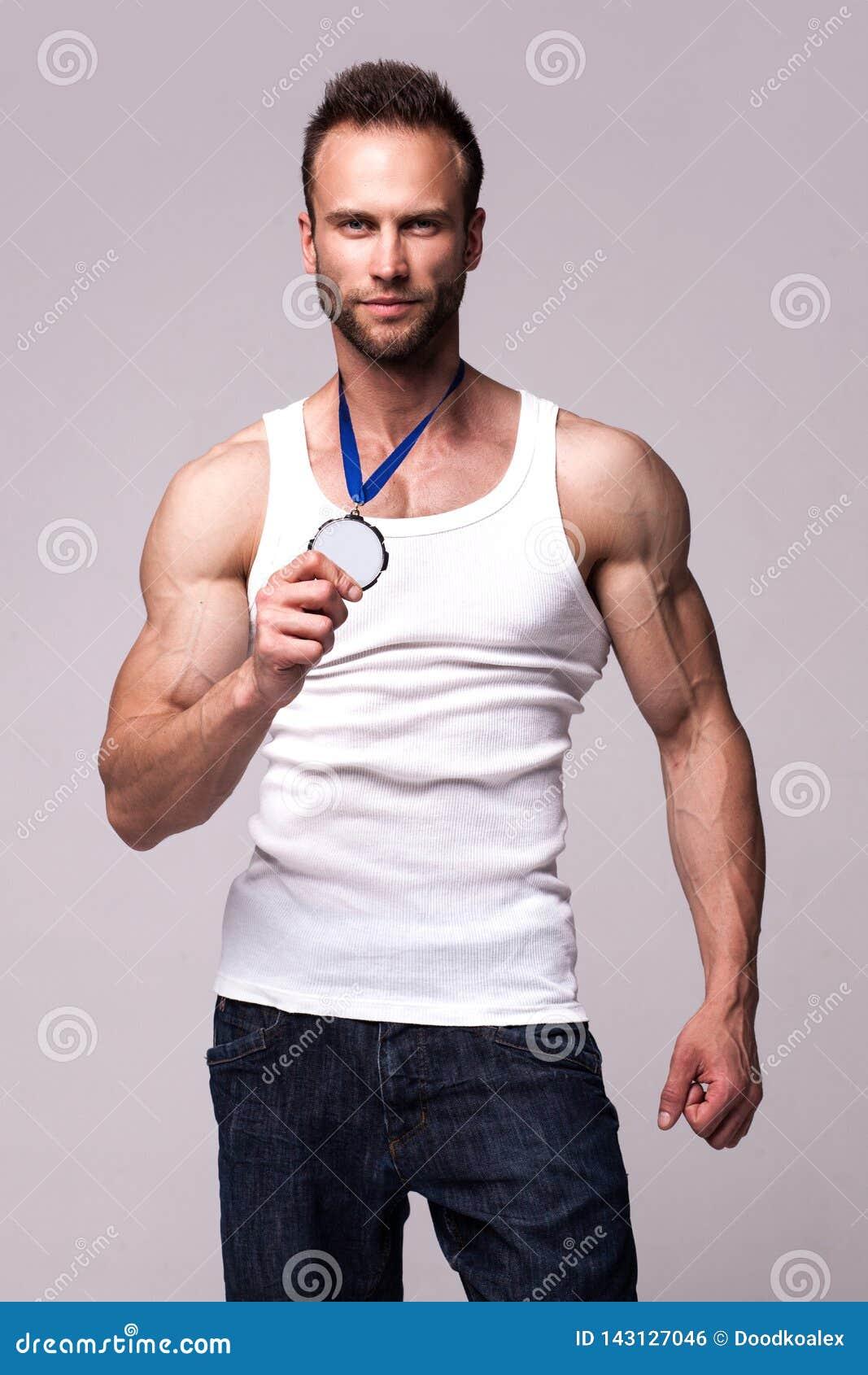 Portret van de atletische mens in wit onderhemd met kampioenenmedaille