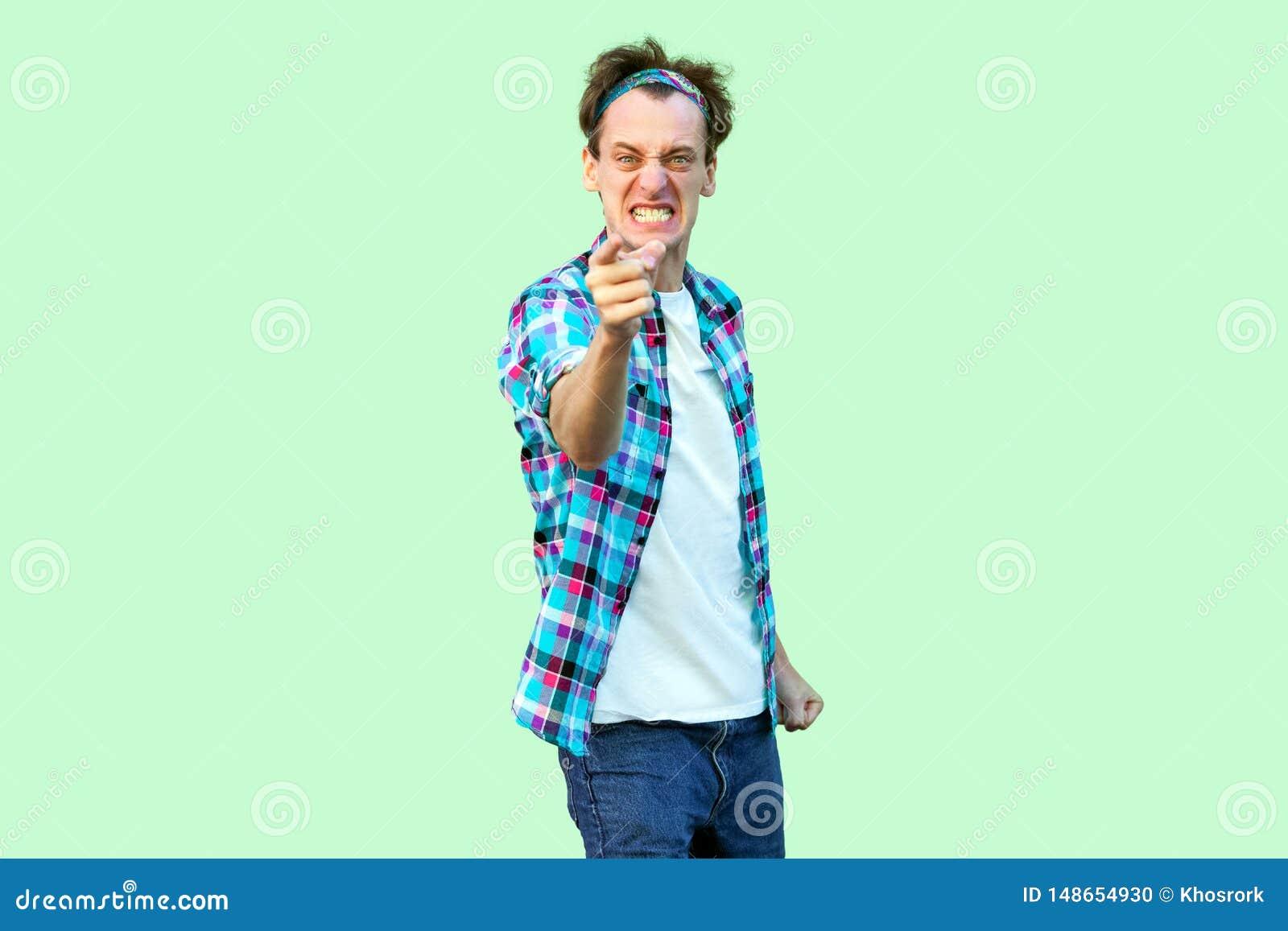 Portret van de boze zenuwachtige jonge mens in toevallig blauw geruit overhemd en hoofdband die, tanden dichtklemmen, en beschuld