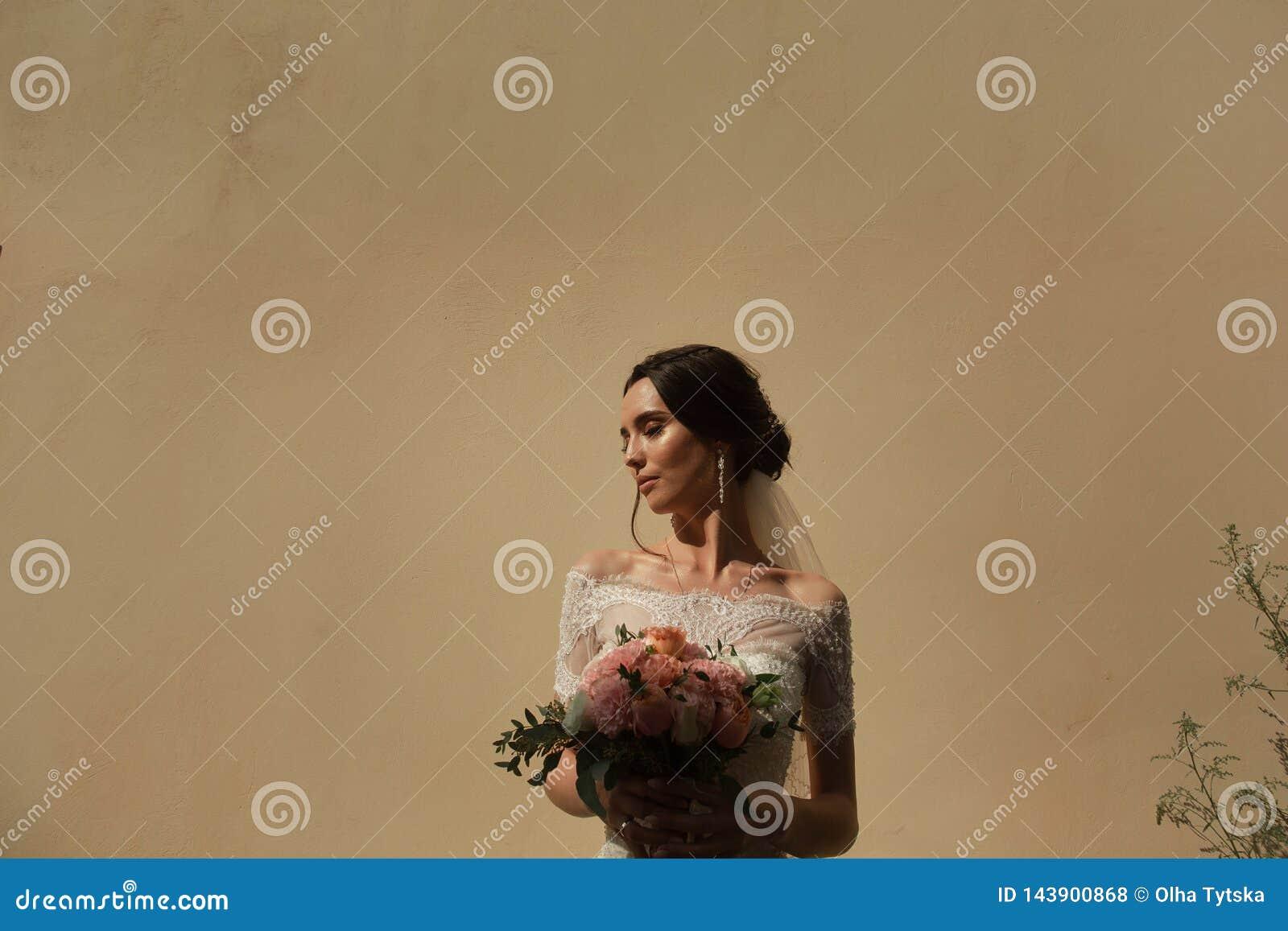 Portret van de bruid met een bos van bloemen op de achtergrond van de muur