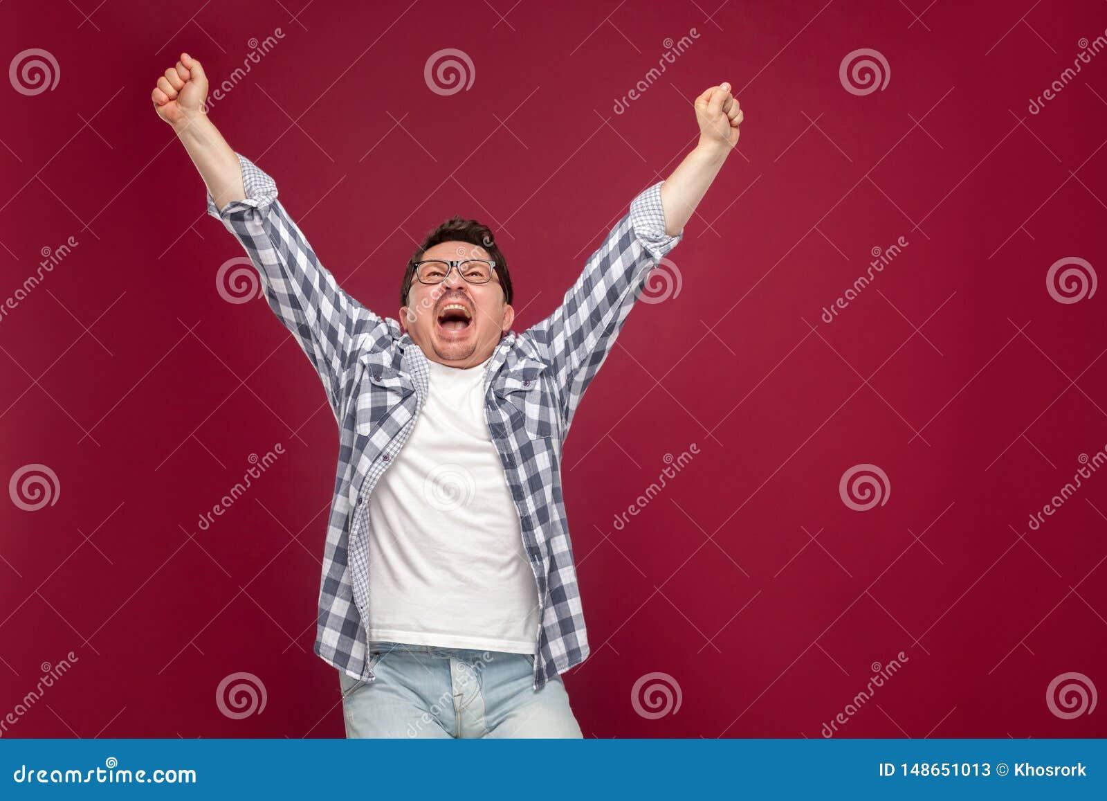 Portret van de gelukkige knappe midden oude mens in toevallig geruit overhemd, oogglazen die holdingshanden opstaan die, gillen e