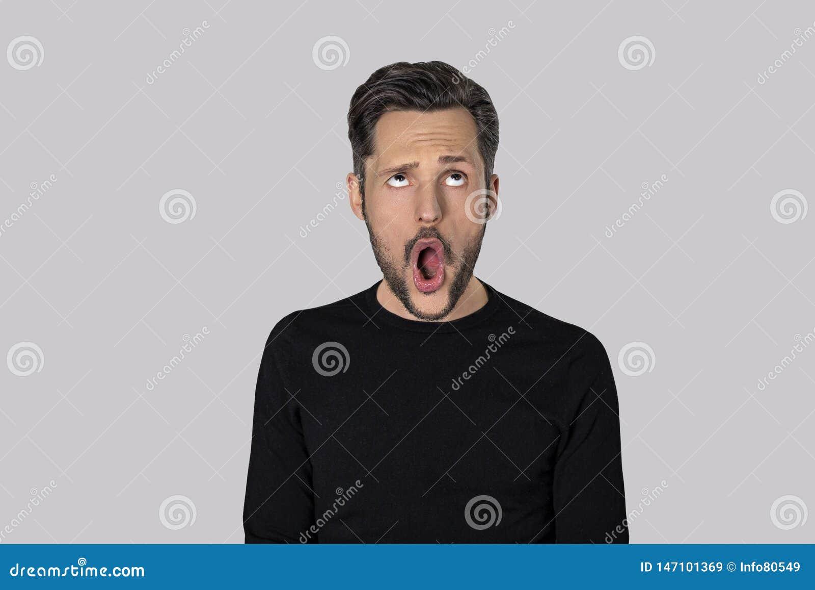 Portret van de jonge mens met een grappige uitdrukking die op grijze achtergrond wordt geïsoleerd