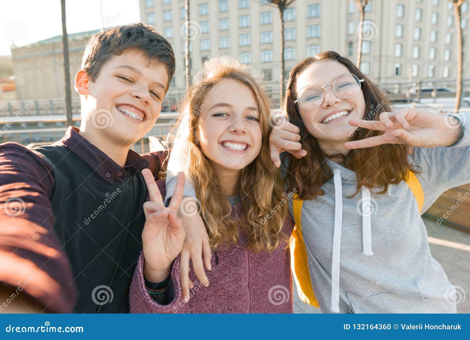 Portret van de jongen van drie tienervrienden en twee meisjes die en een selfie in openlucht glimlachen nemen Stadsachtergrond, g