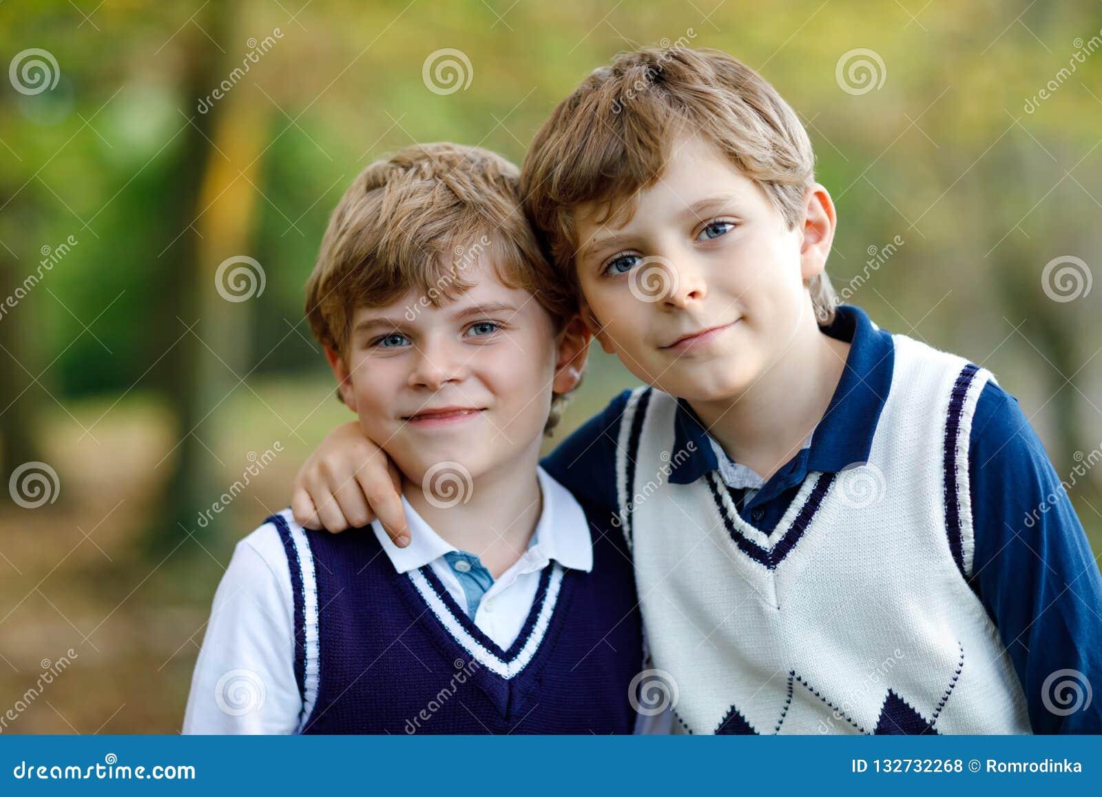 Portret van de jongens die van weinig schooljonge geitjes in bos Gelukkige kinderen, beste vrienden en siblings zitten die pret o