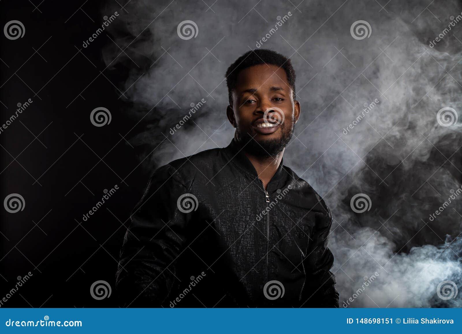Portret van de knappe jonge Afrikaanse mens op zwarte achtergrond