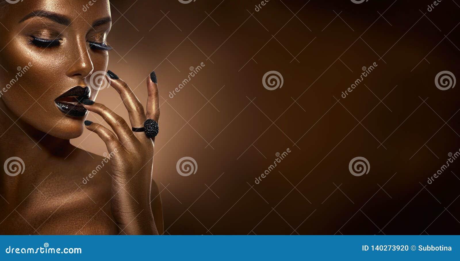 Portret van de de manierkunst van het schoonheids het zwarte meisje over donkere bruine achtergrond Professionele make-up en mani