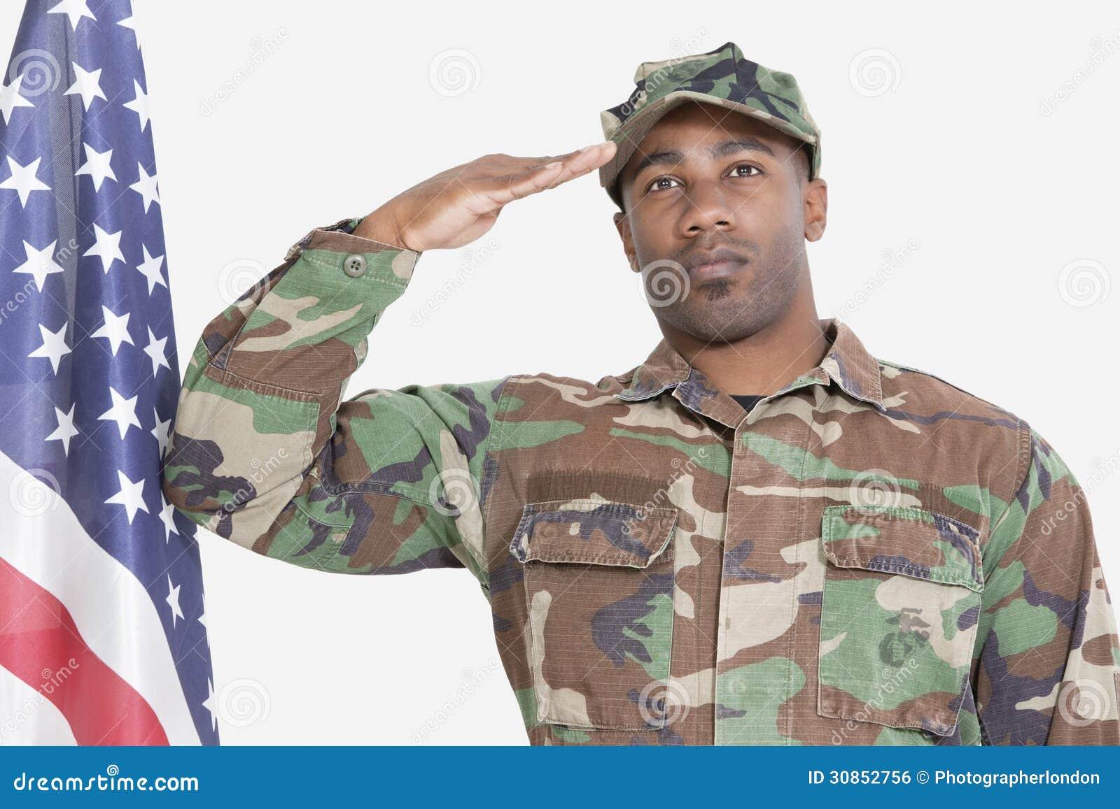 Portret van de militair die van de V.S. Marine Corps Amerikaanse vlag over grijze achtergrond groeten
