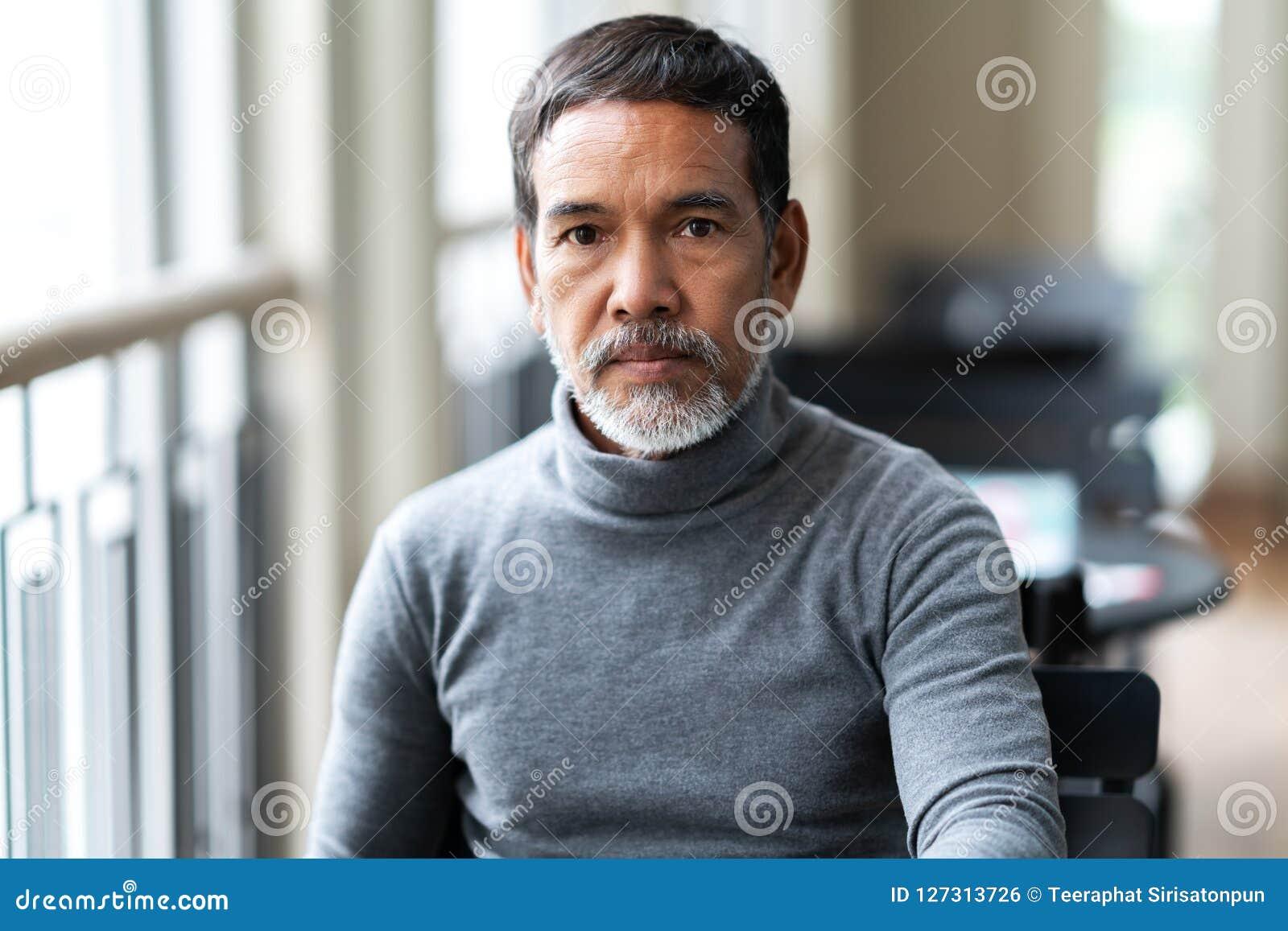 Portret van de ongelukkige boze rijpe Aziatische mens die met modieuze korte baard cemera met negatieve verdacht bekijken