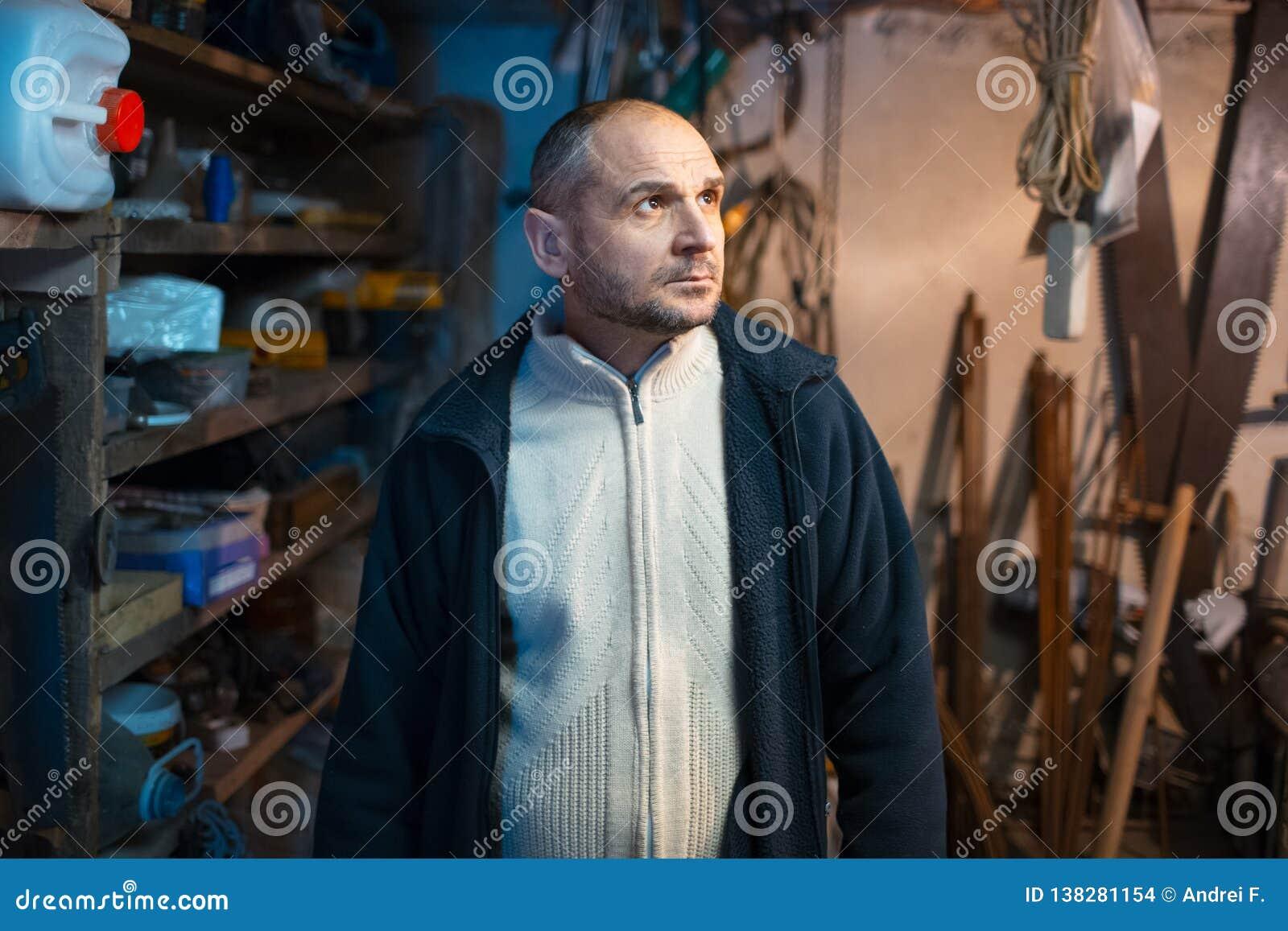Portret van de peinzende volwassen mens in zijn workshopruimte