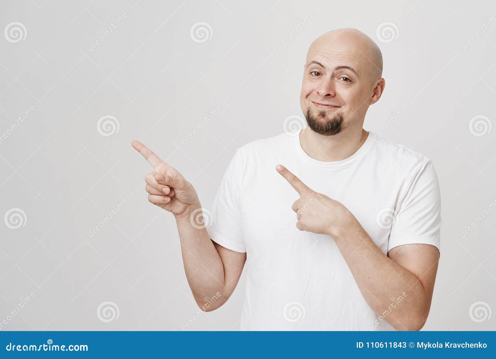 Portret van de tevreden aantrekkelijke kale Kaukasische mens in witte t-shirt die en links met wijsvingers glimlachen richten