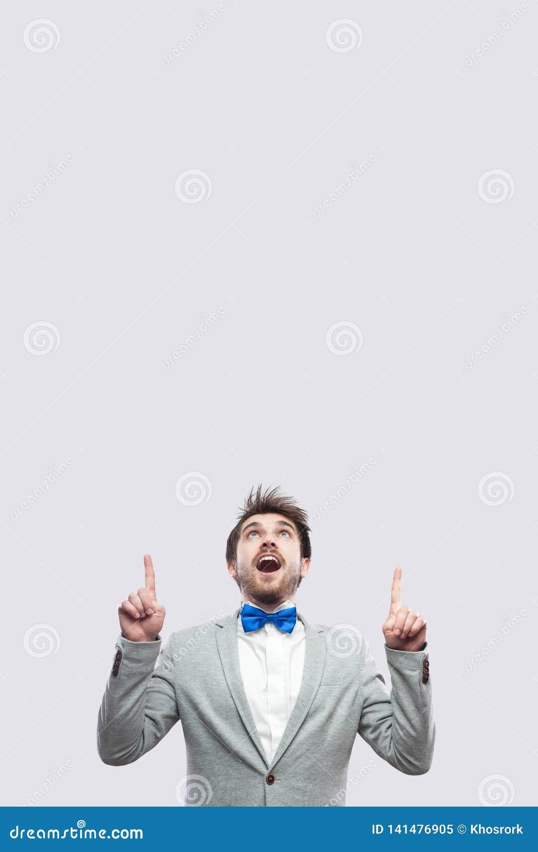 Portret van de verbaasde knappe gebaarde mens in toevallig grijs kostuum en blauwe vlinderdas status bekijkend en richtend op omh