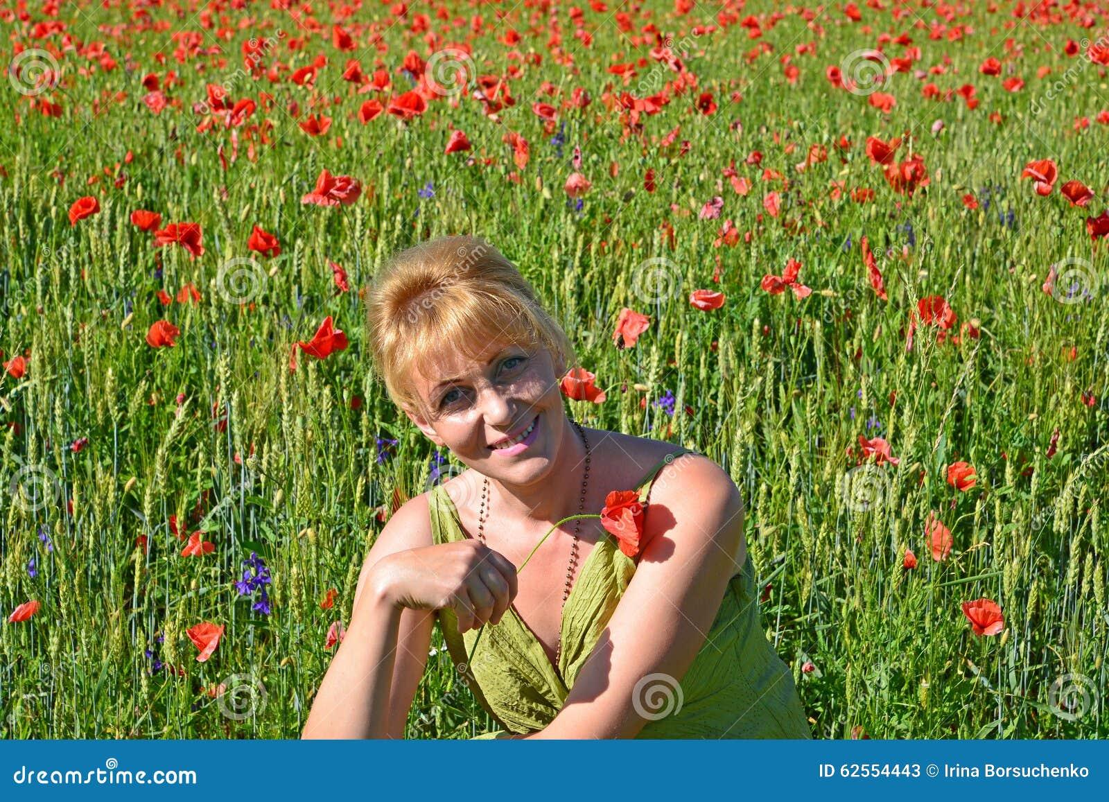 Portret van de vrouw van gemiddelde jaren met rode papaver in een hand stock afbeelding - Renovateer een huis van de jaren ...
