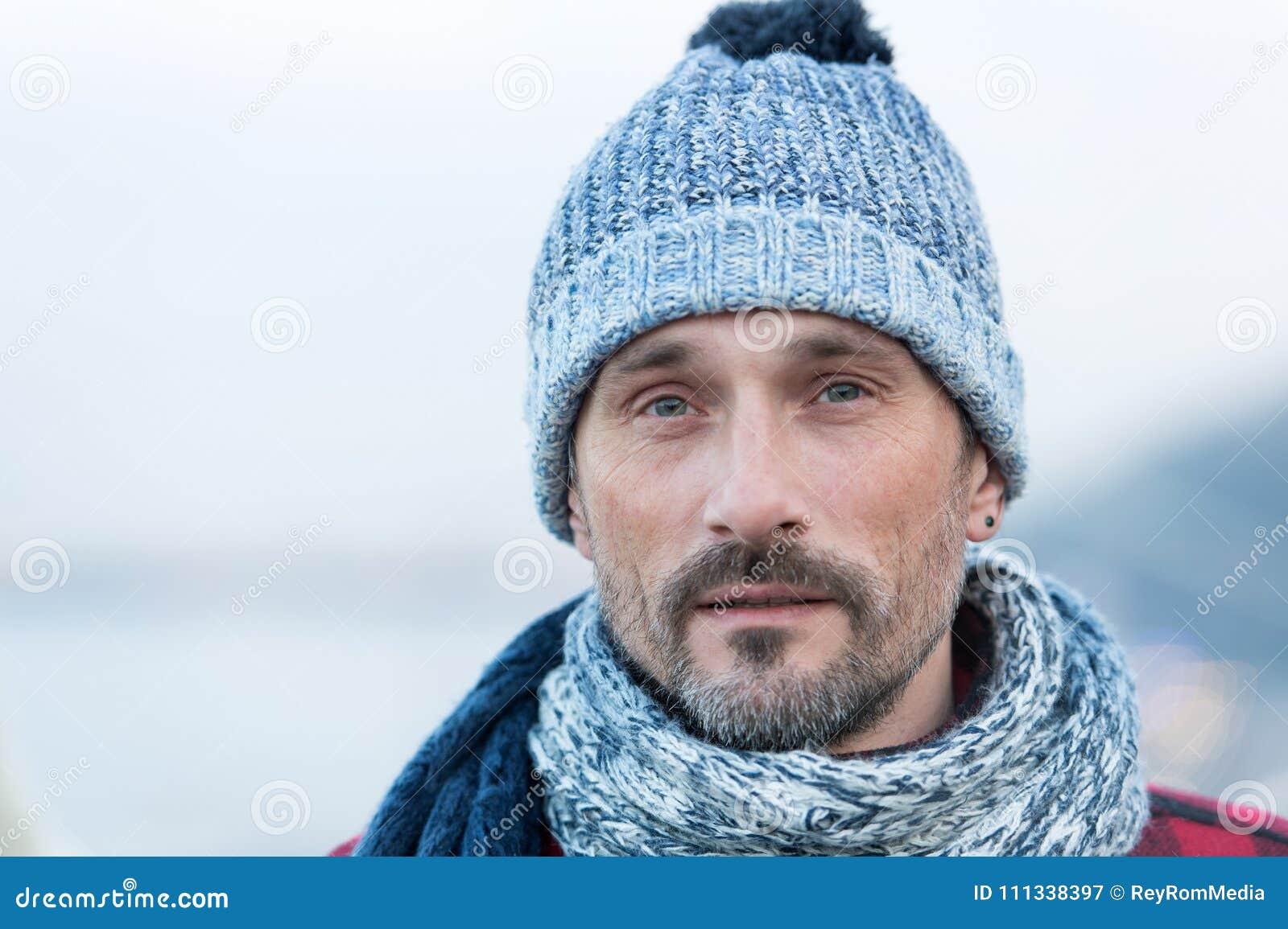 Portret van de witte mens in de winter gebreide hoed en sjaal Sluit omhoog van gebaarde kerel in blauw-witte hoed en sjaal