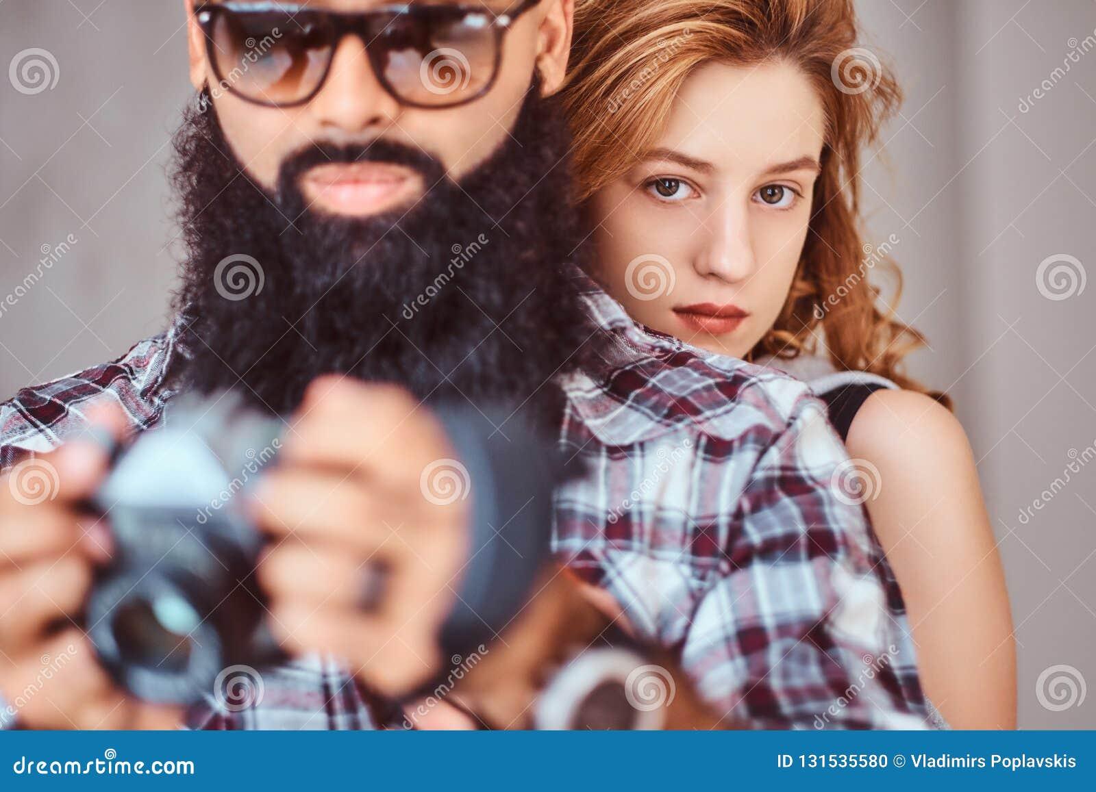 Portret van een Arabisch gebaard mannetje een camera houden en zijn mooi roodharigemeisje die