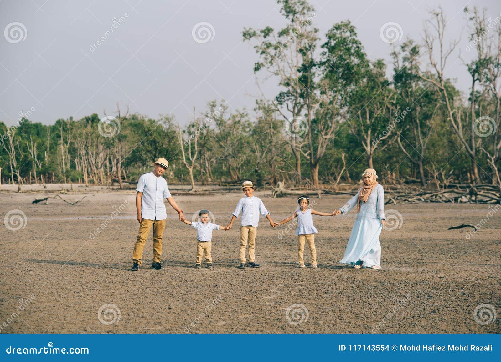 Portret van een Aziatische Maleise familie die zeer gelukkig samen in openlucht houdend hand kijken