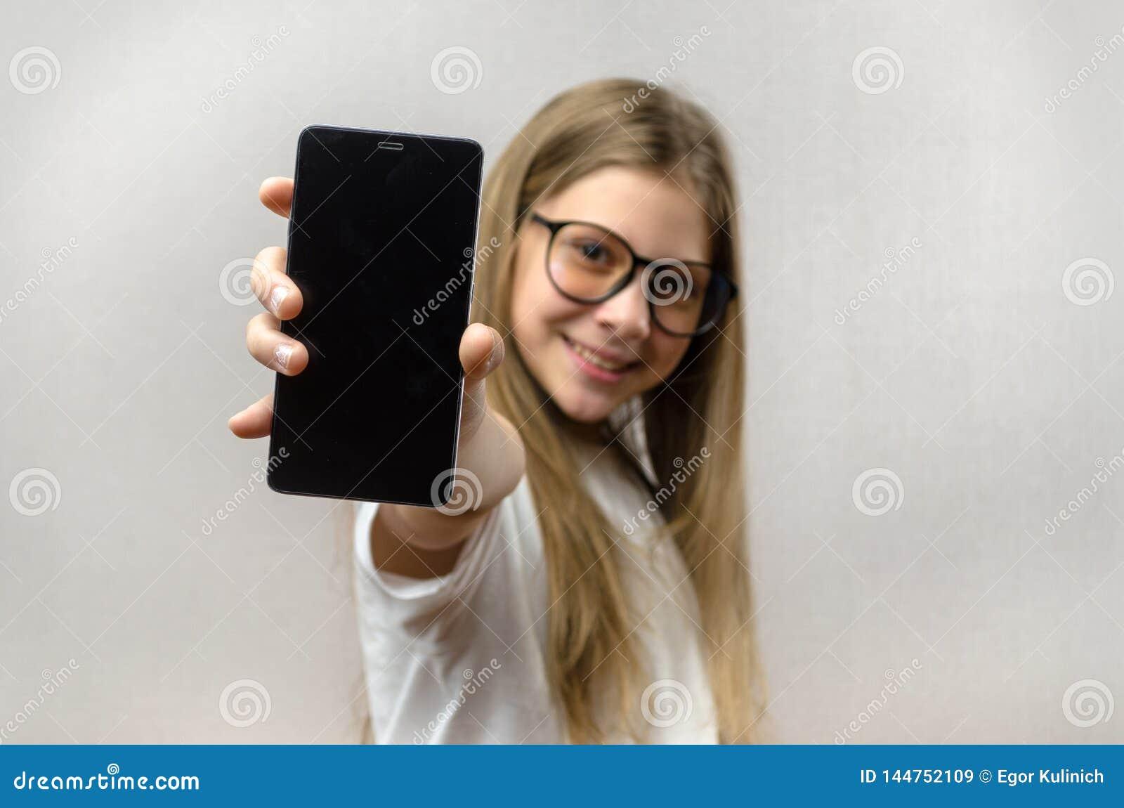 Portret van een blondemeisje met een smartphone in haar hand Slimme technologie Mobiele aansluting Smartphone van kinderen apps