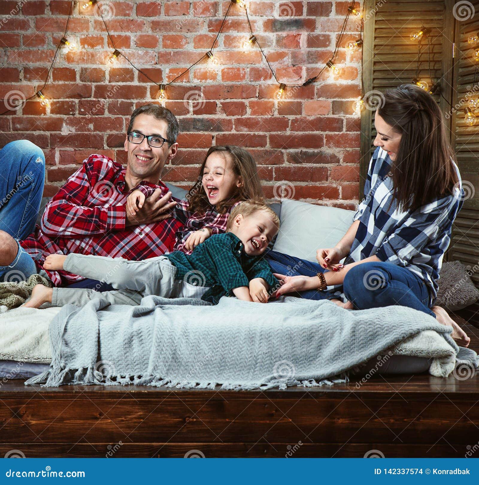 Portret van een cheerrful familie die in modieuze binnenlands ontspannen