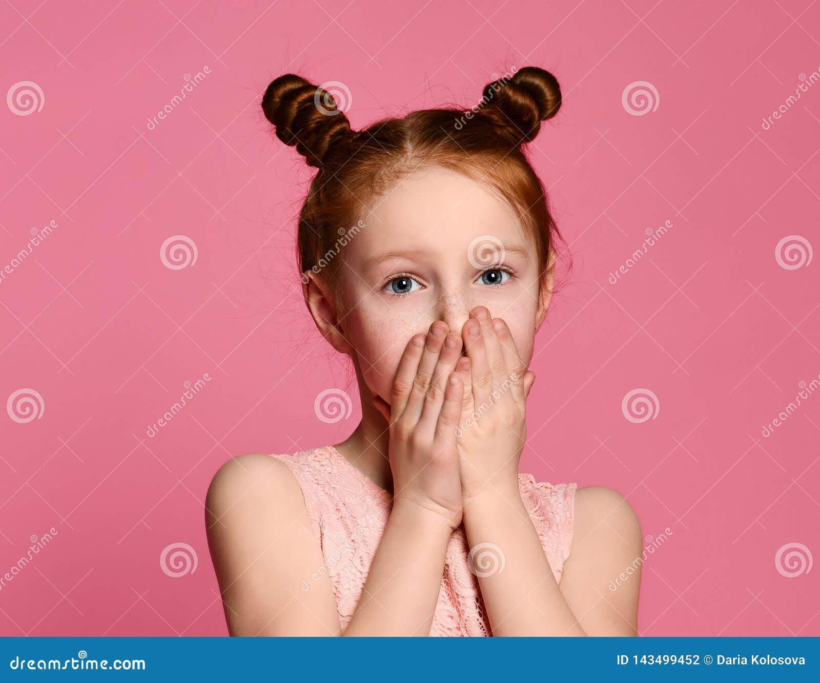 Portret van een ernstig jong gembermeisje die mond behandelen met beide handen die geheim houden