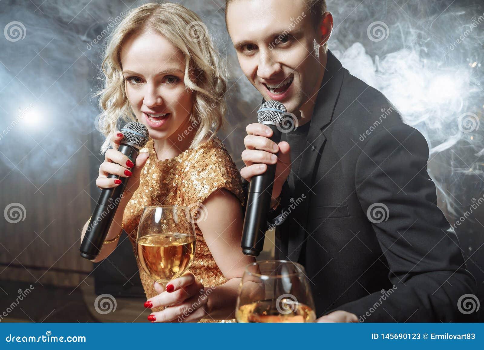 Portret van een gelukkig jong paar met microfoons en glazen in een karaokebar
