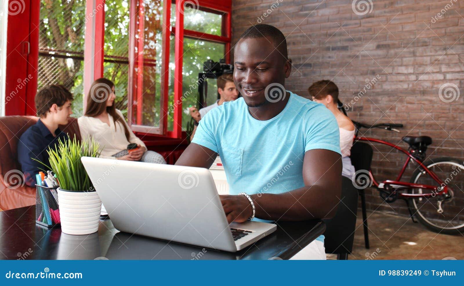 Portret van een gelukkige Afrikaanse Amerikaanse ondernemer die computer in bureau tonen