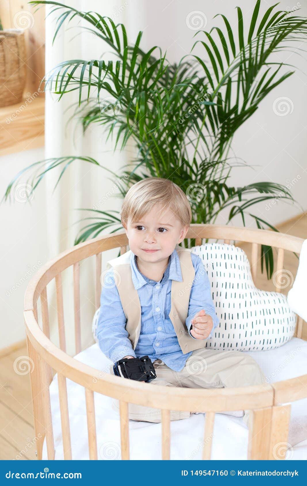 Portret van een gelukkige jongen die in een babywieg spelen De jongen zit alleen in een voederbak in het kinderdagverblijf Eenzaa