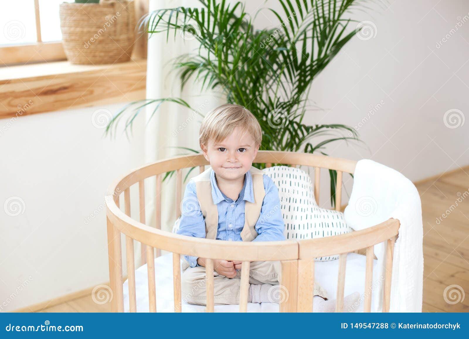 Portret van een gelukkige jongen die in een babywieg spelen De jongen zit alleen in een voederbak in het kinderdagverblijf Het ee