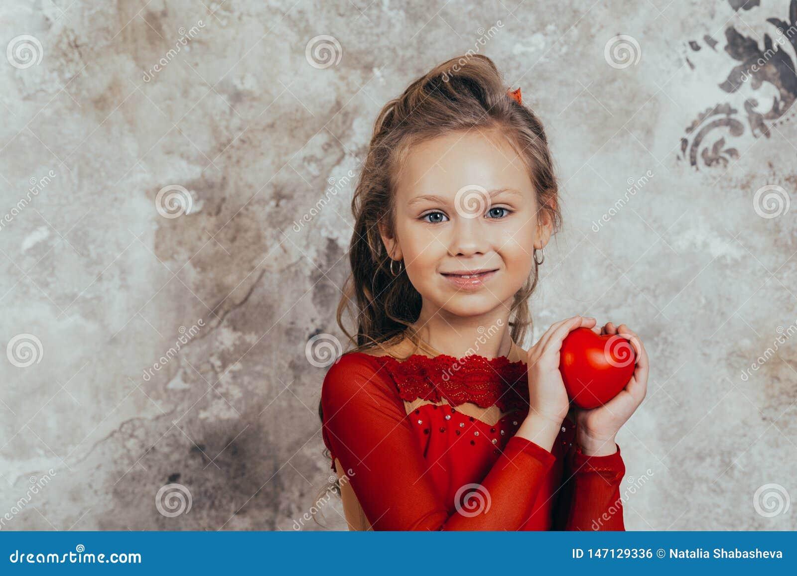 Portret van een glimlachend jong meisje in een rode kleding en met een mooi kapsel met een hart