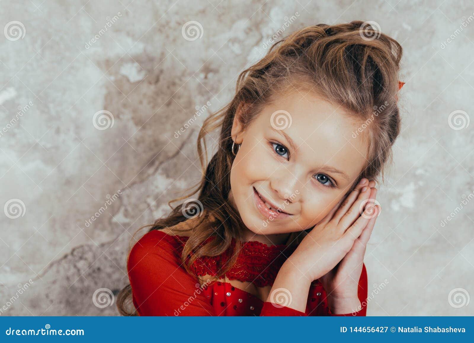 Portret van een glimlachend jong meisje in een rode kleding en met een mooi kapsel Het schot van de studio