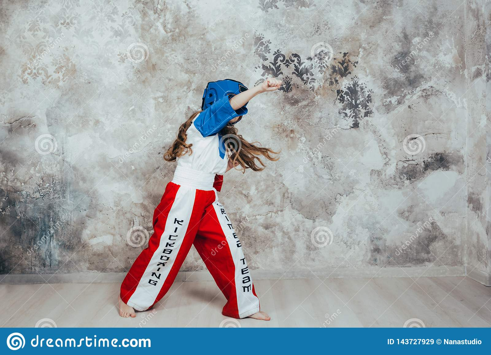 Portret van een glimlachend jong vrouwelijk taekwondomeisje tegen een grungemuur