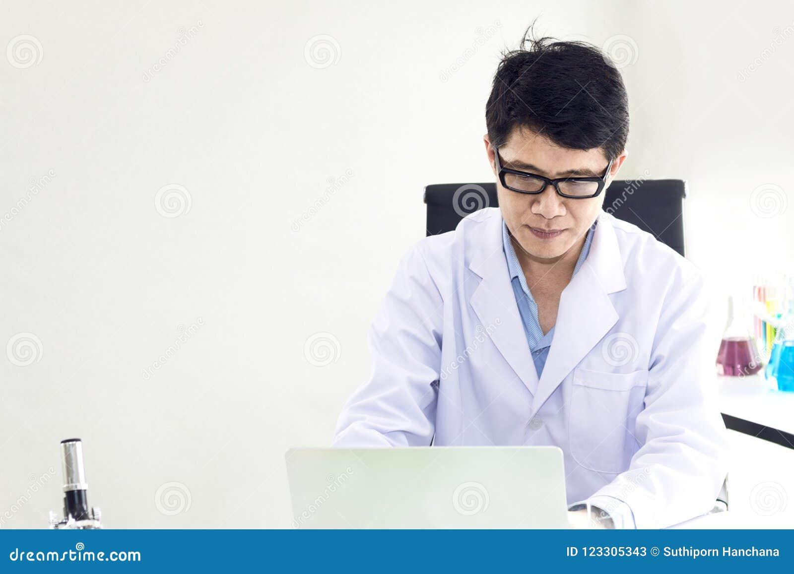 Portret van een glimlachende rijpe wetenschapper in een witte laag met glas