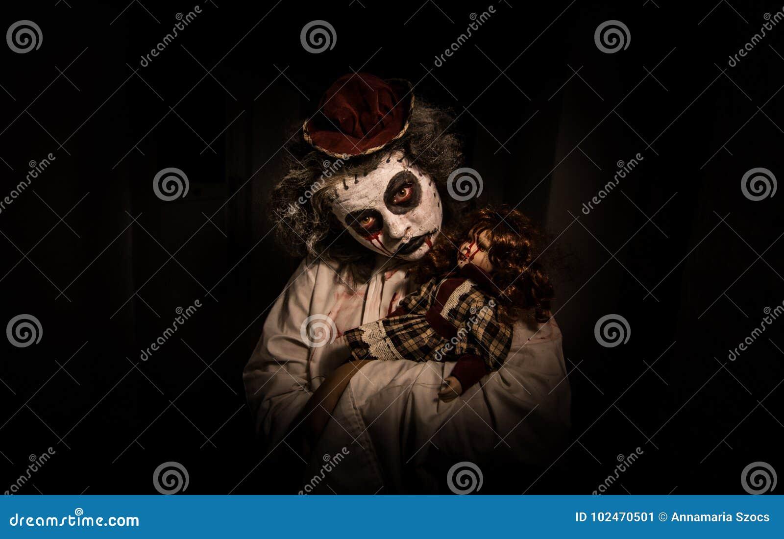 Portret van een griezelig meisje met bloedige pop