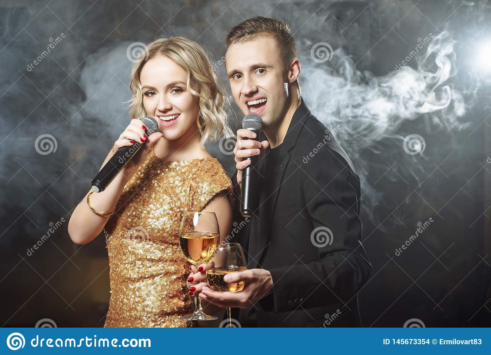 Portret van een jong gelukkig paar die in een microfoon in een club zingen