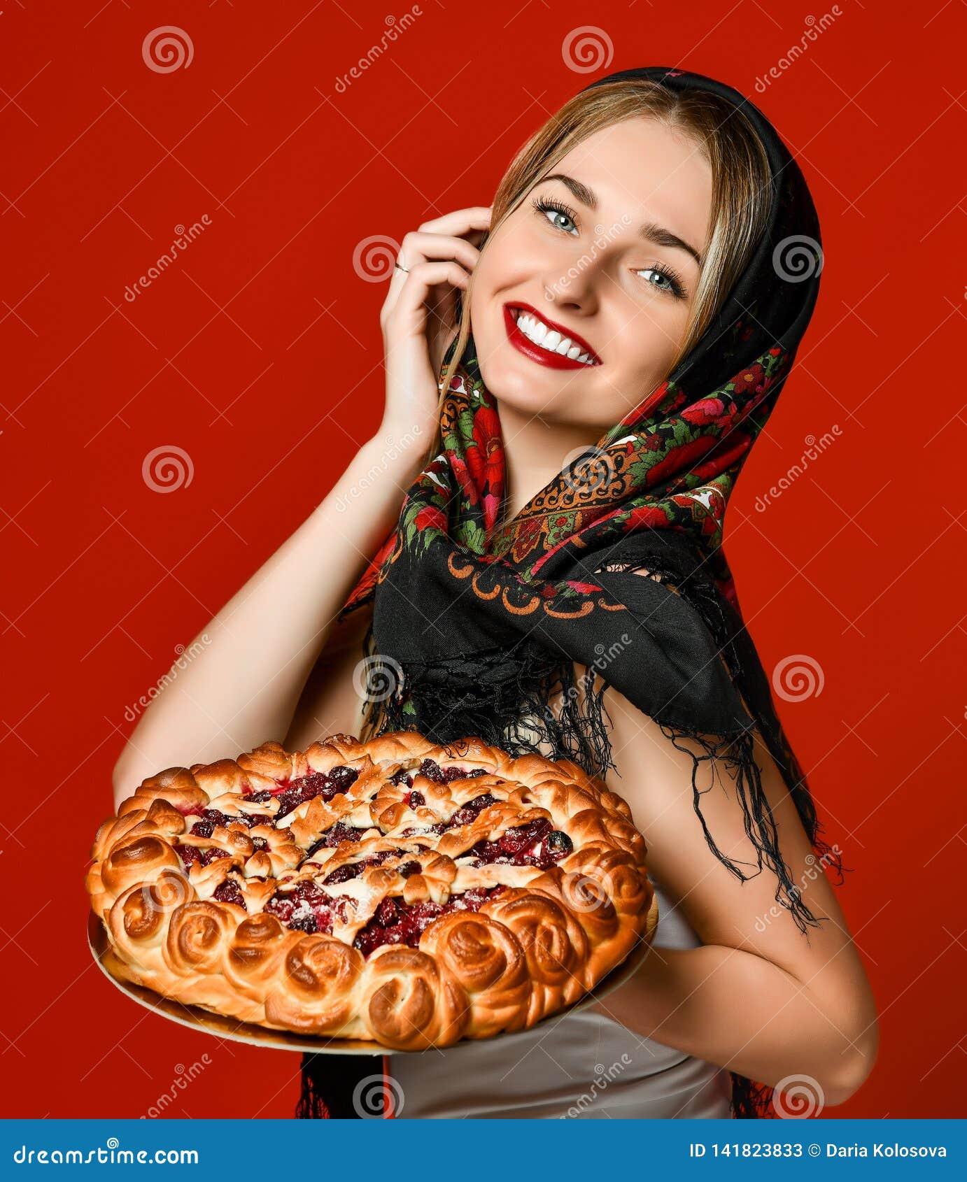 Portret van een jong mooi blonde in headscarf die een heerlijke eigengemaakte bessenpastei houden