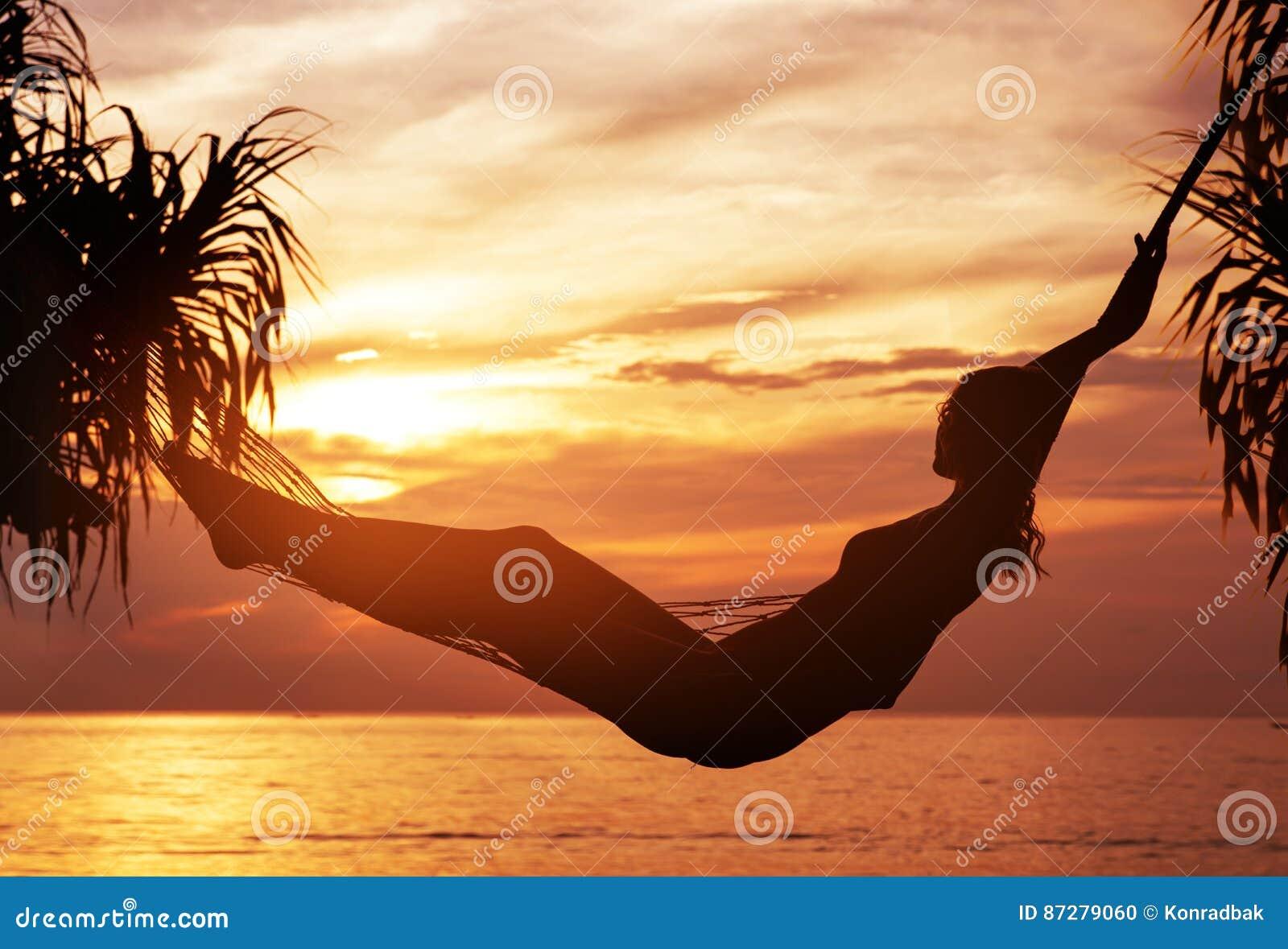 Portret van een jonge, aantrekkelijke vrouw die op een zonsondergang letten