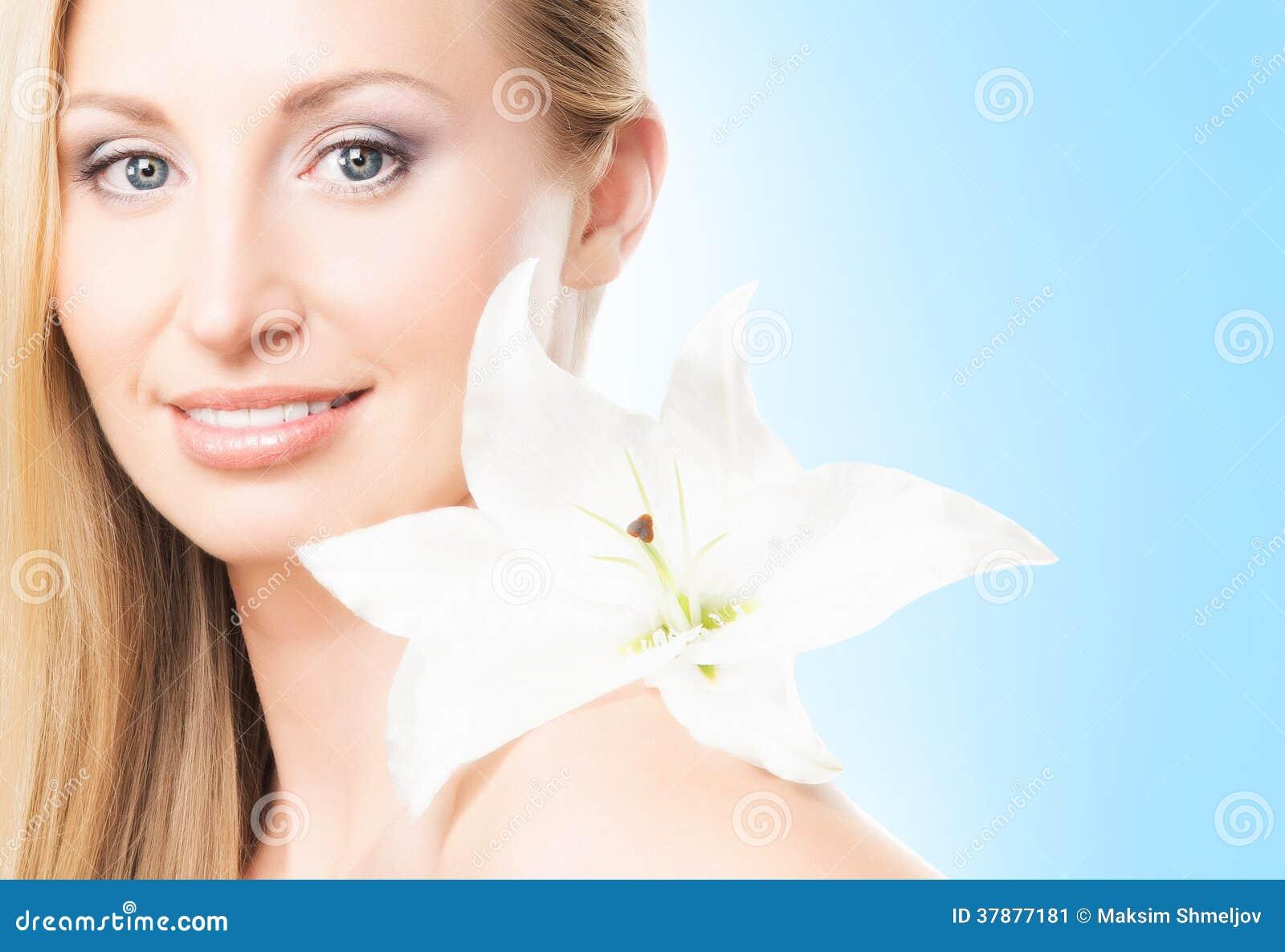 Portret van een jonge blonde vrouw met een bloem