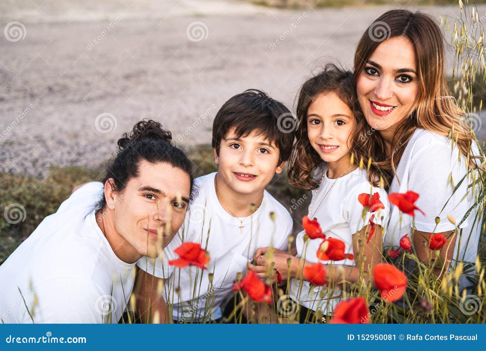 Portret van een jonge familie die en gelukkige de camera op de buitenkant glimlachen bekijken
