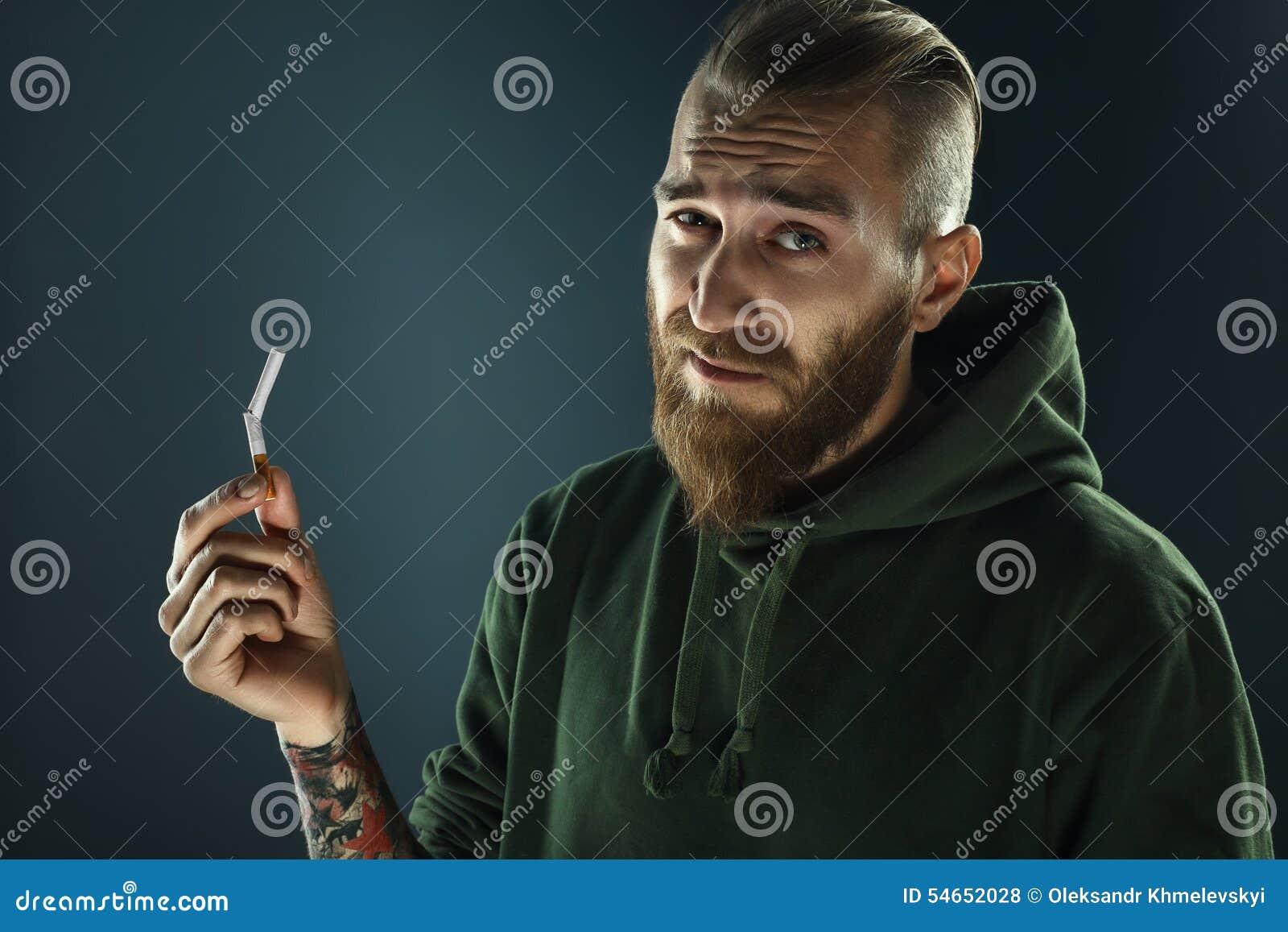Portret van een jonge kerel ophouden met rokend