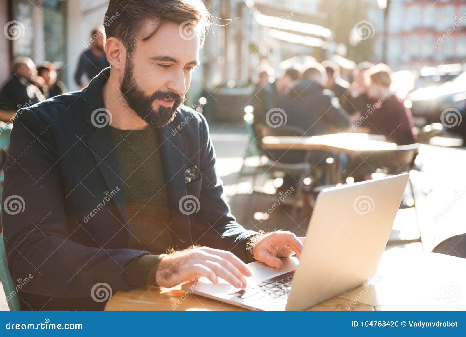 Portret van een jonge modieuze mens die aan laptop computer werken