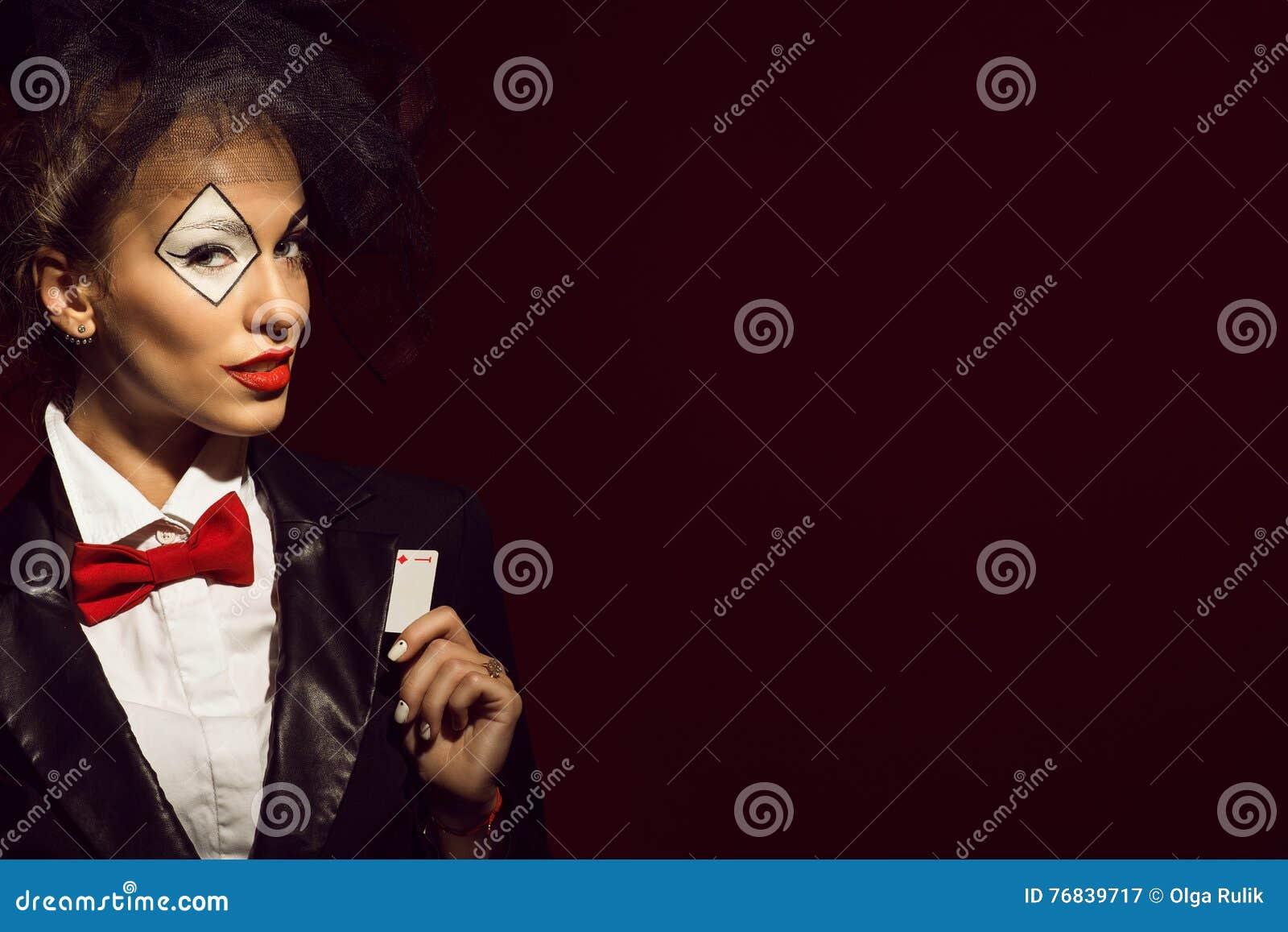 Portret van een jonge mooie damecroupier in een beeld die van joker een aaskaart verbergen