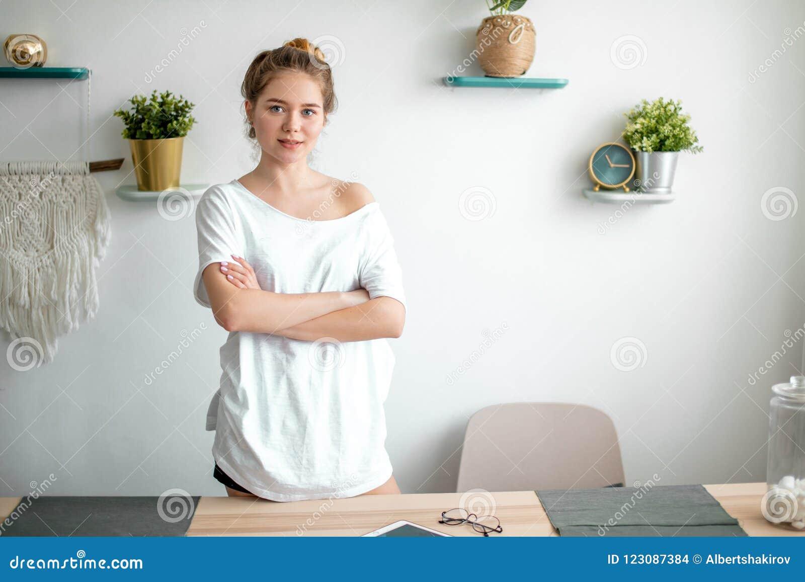 Portret van een jonge mooie vrouw in toevallige uitrusting die zich met gekruiste wapens bevinden