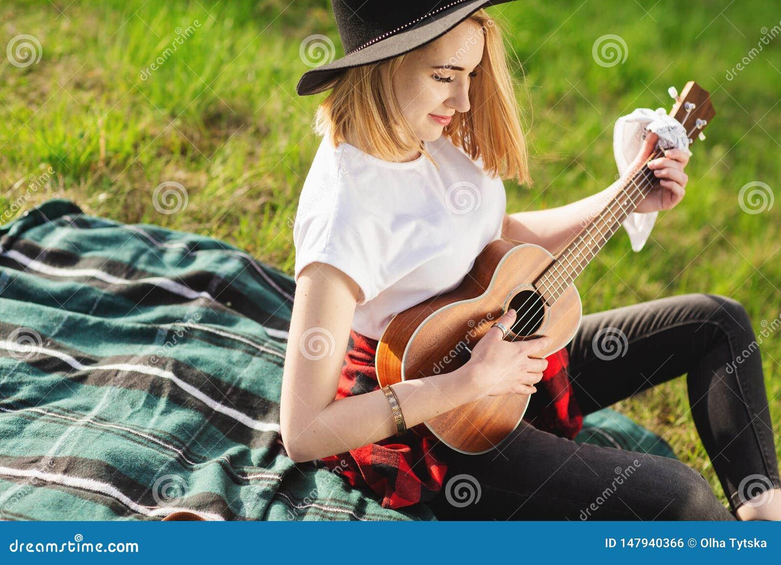 Portret van een jonge mooie vrouw in een zwarte hoed Meisjeszitting op de het gras en het spelen gitaar