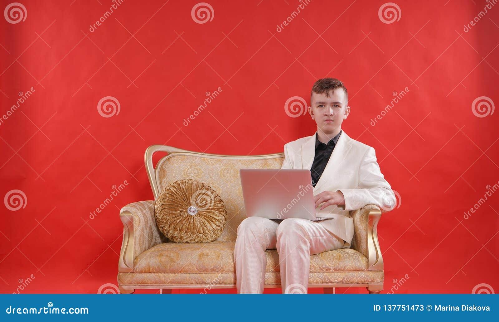 Portret van een jonge tienermens die wit bureaukostuum dragen en op de gouden luxebank zitten op rode achtergrond hij werkt aan L