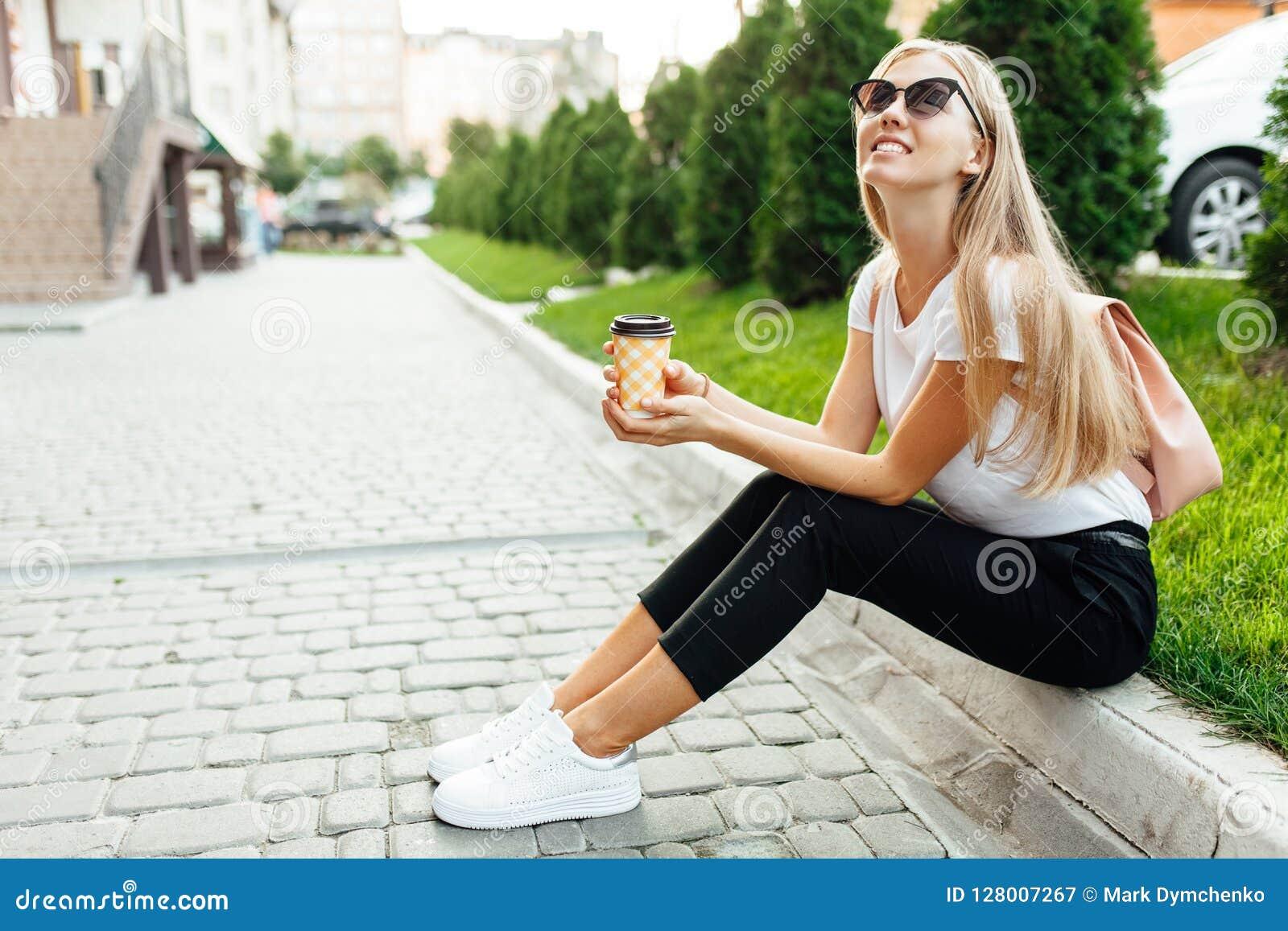 Portret van een jonge vrouw die zonnebril in openlucht met coffe dragen