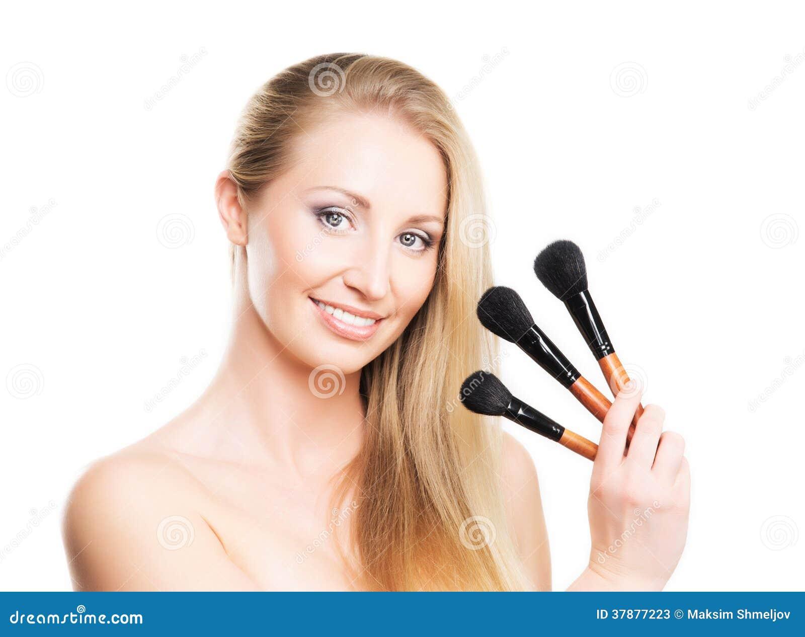 Portret van een jonge vrouw met make-upborstels