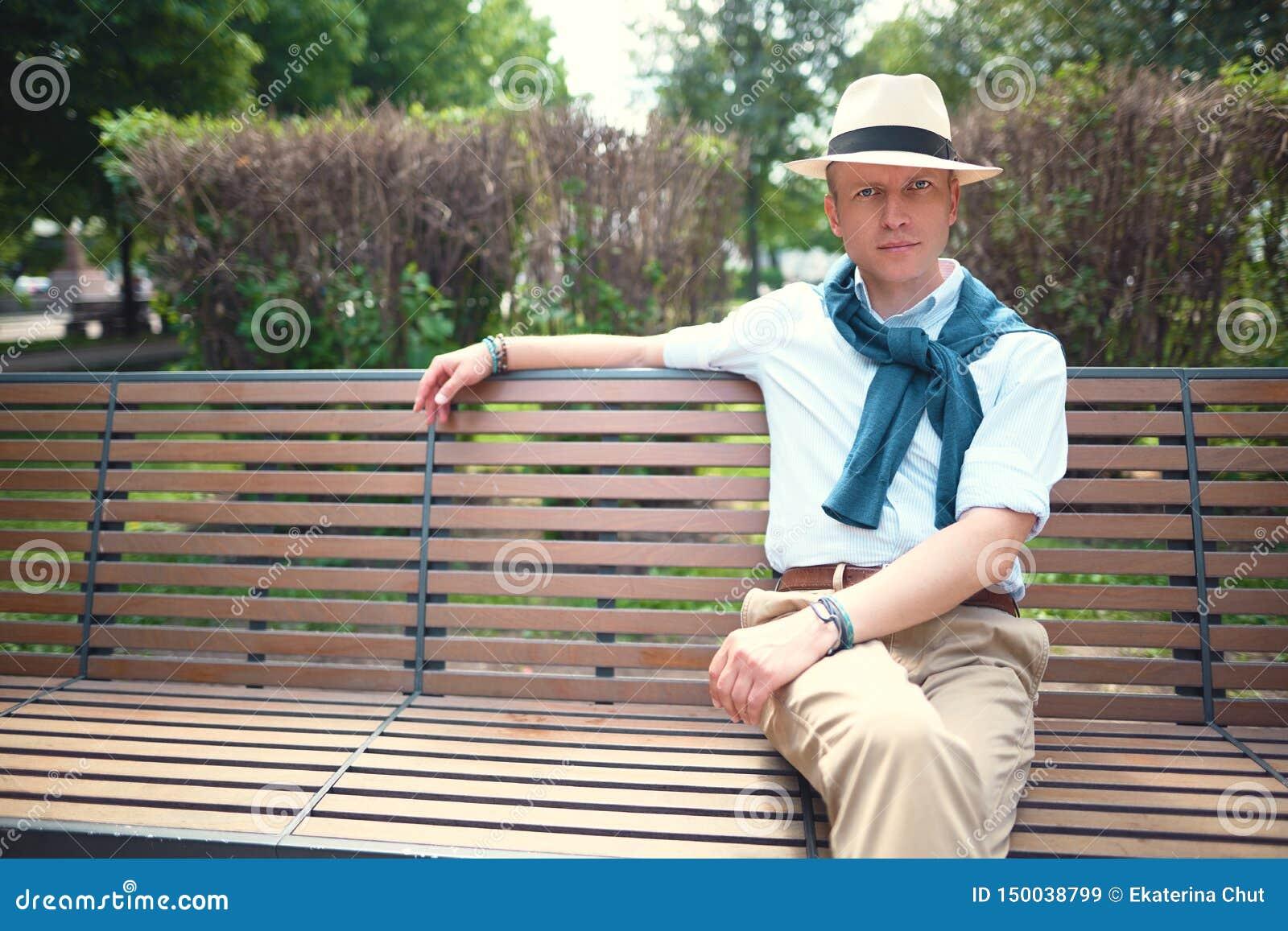 Portret van een kerelzitting op een parkbank