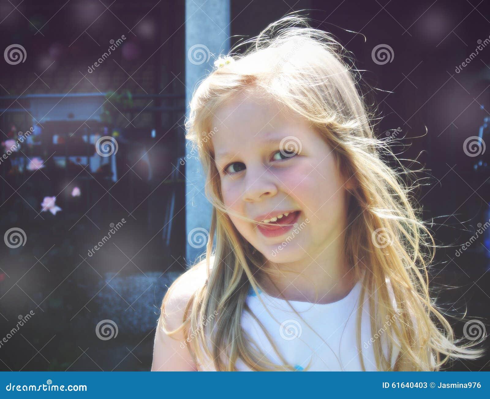 Portret van een klein blonde glimlachend meisje; zachte retro stijl